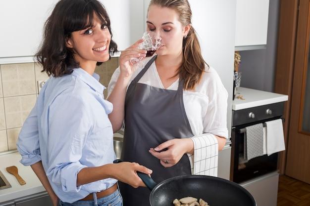Donna che cucina cibo guardando fotocamera in piedi vicino ai bicchieri di vino in cucina Foto Gratuite