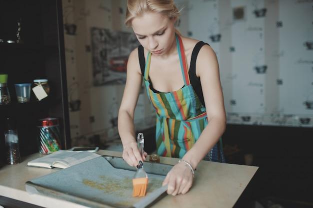Donna che cucina pizza in cucina Foto Gratuite