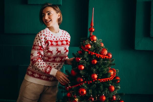 Donna che decora l'albero di natale con i giocattoli rossi Foto Gratuite
