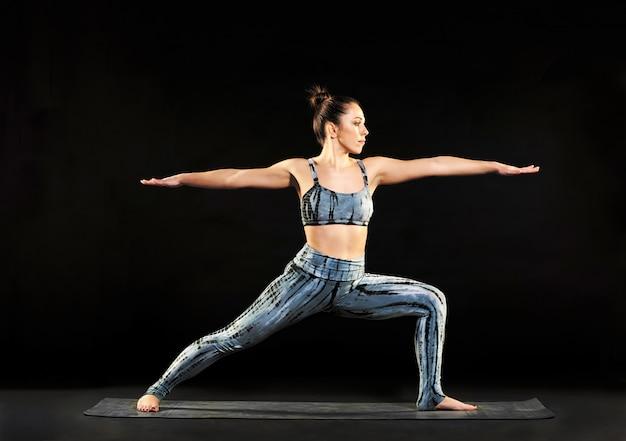 Donna che dimostra la posa del guerriero 2 nello yoga Foto Premium