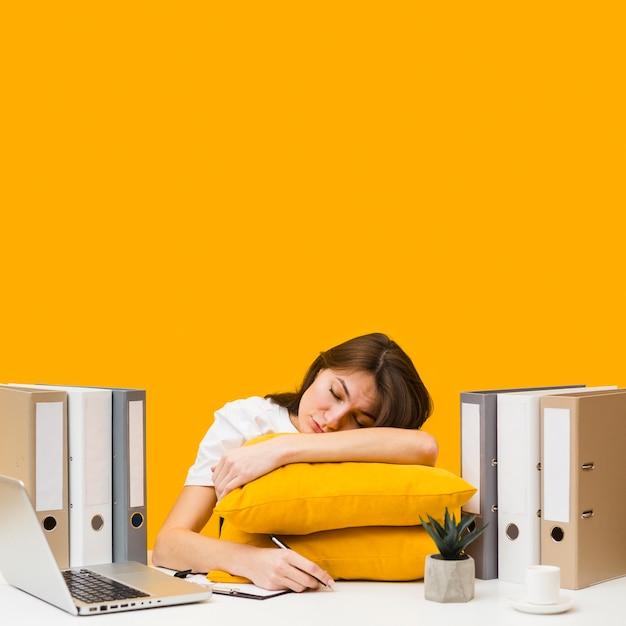 Donna che dorme sui cuscini in cima alla sua scrivania Foto Gratuite