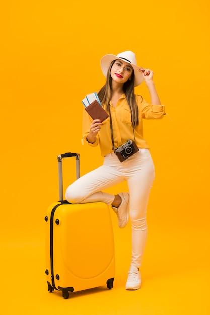 Donna che è pronta per le vacanze con i bagagli e gli elementi essenziali di viaggio Foto Gratuite