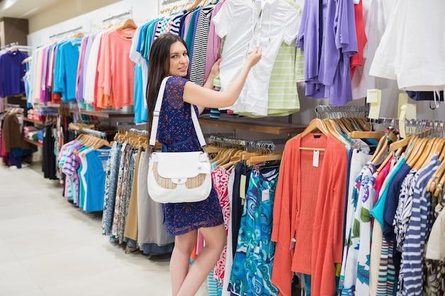 Donna che esamina il cartellino del prezzo mentre si tiene i vestiti Foto Premium