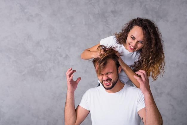Donna che esegue le dita attraverso i capelli dell'uomo ...
