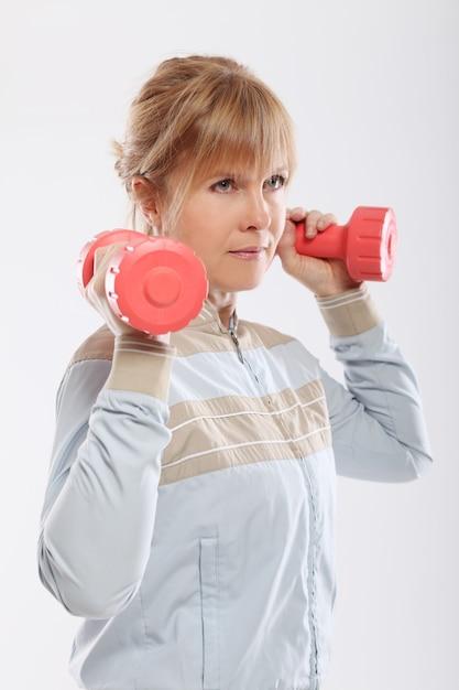 Donna che fa esercizio con la vista delle teste di legno dalla parte posteriore Foto Gratuite