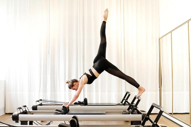 Donna che fa esercizio di yoga del luccio a gamba singola Foto Premium