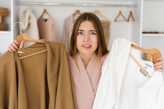 Donna che fa fatica a decidere cosa indossare Foto Gratuite
