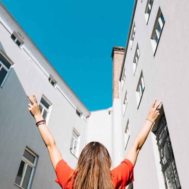 Donna che fa gesto di pace vicino edificio residenziale Foto Gratuite