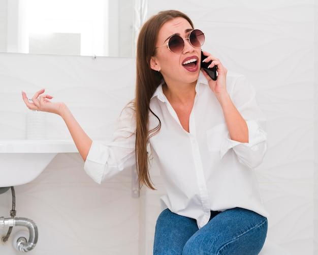 Donna che fa i fronti e che parla sul telefono Foto Gratuite