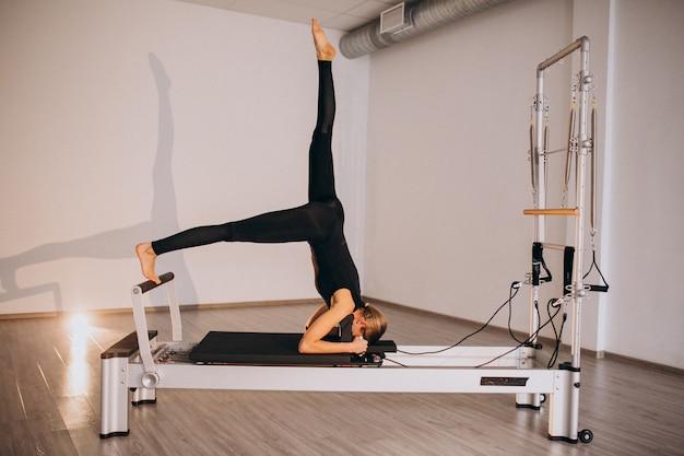 Donna che fa pilates su un riformatore Foto Gratuite