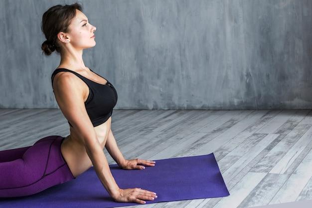 Donna che fa respiri profondi in un tratto di cobra Foto Gratuite