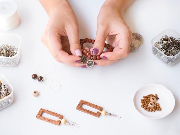 Donna che fa un braccialetto di perle Foto Gratuite