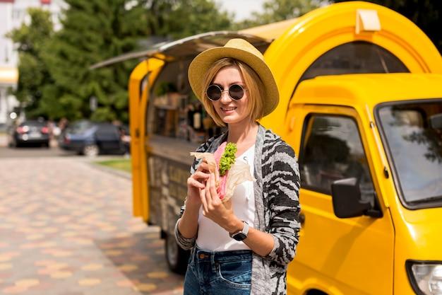 Donna che fa una pausa il camion dell'alimento Foto Gratuite