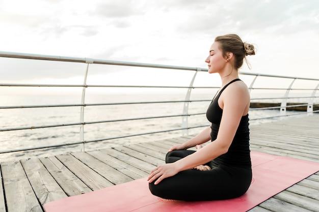 Donna che fa yoga e meditazione vicino al mare all'alba Foto Premium