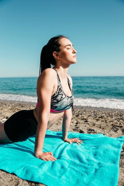 Donna che fa yoga in spiaggia Foto Gratuite