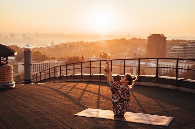 Donna che fa yoga sul tetto di un grattacielo in grande città. Foto Gratuite