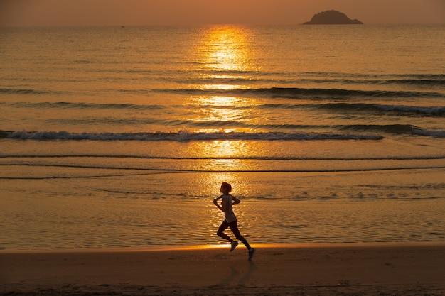 Donna che funziona sulla spiaggia all'alba Foto Premium