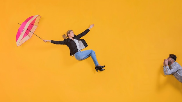 Donna che galleggia in aria con un ombrello Foto Gratuite