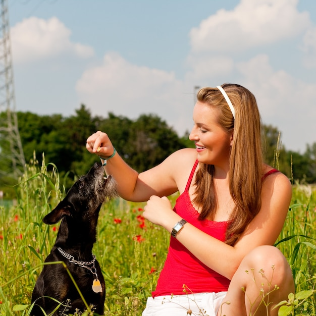 Donna che gioca con il suo cane in un prato Foto Premium
