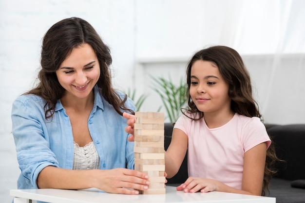 Donna che gioca con sua figlia un gioco di imbarco Foto Gratuite