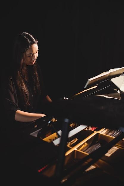 Donna che gioca un piano nello studio di musica Foto Gratuite