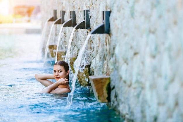 Donna che gode delle vacanze di vacanza al lussuoso resort sulla spiaggia con piscina e lansdcape tropicale vicino alla spiaggia Foto Premium