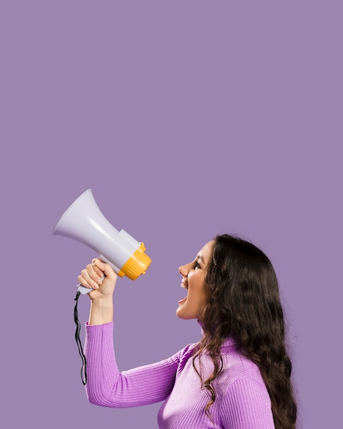 Donna che grida nel megafono e nello spazio della copia Foto Gratuite