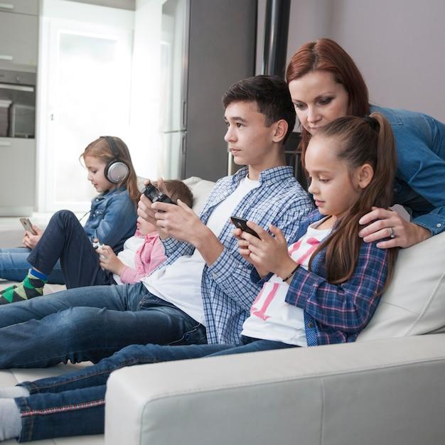 Donna che guarda adolescente e ragazza che giocano ai videogiochi Foto Gratuite