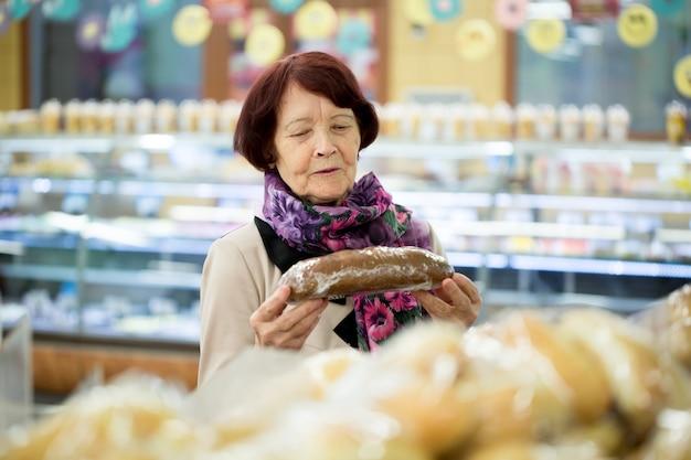 Donna che guarda il pane al negozio del supermercato Foto Premium