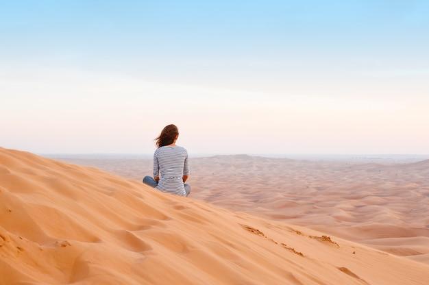 Donna che guarda il tramonto nella sabbia del deserto Foto Premium