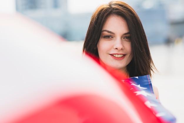 Donna che guarda l'obbiettivo e sorridente sventolando la bandiera americana Foto Gratuite