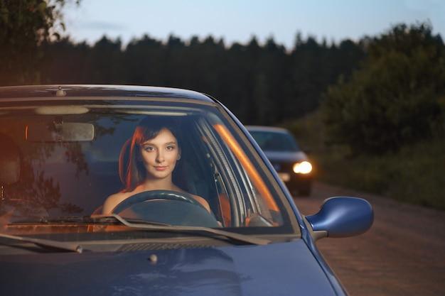 Donna che guida la macchina la sera Foto Premium