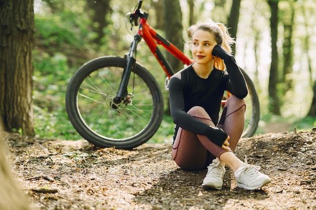 Donna che guida un mountain bike nella foresta Foto Gratuite
