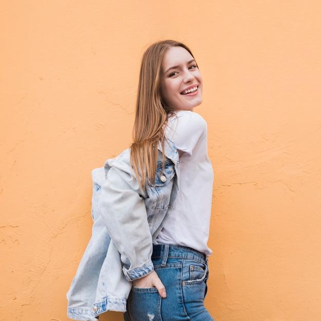 Donna che indossa giacca di jeans e posa vicino al muro beige Foto Gratuite