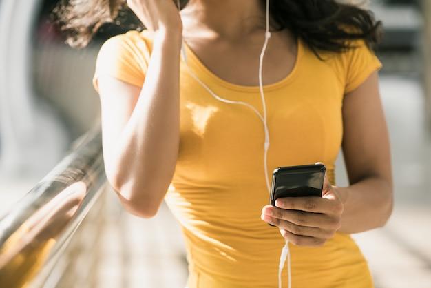 Donna che indossa gli auricolari ascoltando musica da smartphone Foto Premium