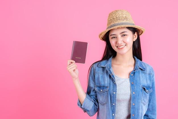 Donna che indossa il cappello da traino in possesso di passaporto ritratto di adolescente sorridente piuttosto felice sul rosa Foto Gratuite