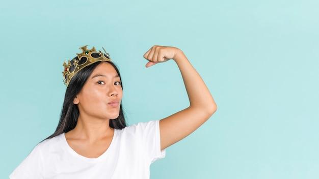 Donna che indossa la corona e mostrando i muscoli Foto Gratuite