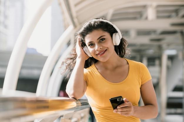 Donna che indossa le cuffie bluetooth ascoltando musica Foto Premium