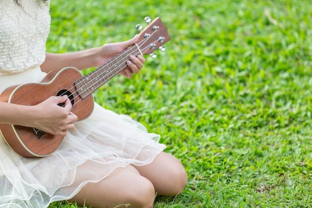 Donna che indossa un abito bianco carino e giocare ukulele Foto Gratuite