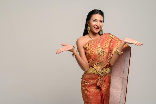 Donna che indossa un abito thailandese che ha fatto un simbolo della mano Foto Gratuite