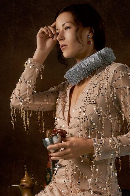 Donna che indossa un colletto elisabettiano e che trasporta un calice pieno di uva Foto Gratuite