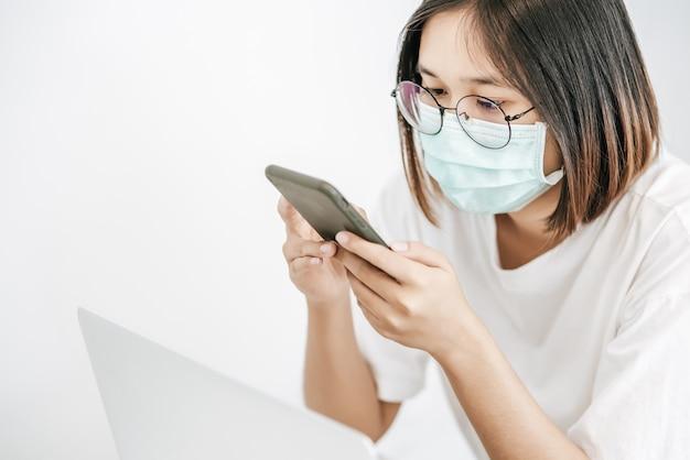 Donna che indossa una maschera sanitaria, giocando uno smartphone e avendo un computer portatile. Foto Gratuite