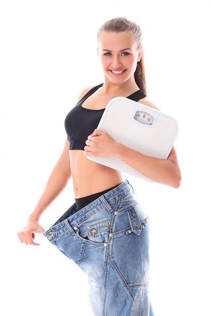 Donna che indossa vecchi jeans dopo la perdita di peso Foto Gratuite