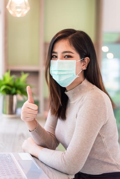 Donna che lavora al computer portatile mentre indossa maschera medica e rinunciare pollici Foto Premium