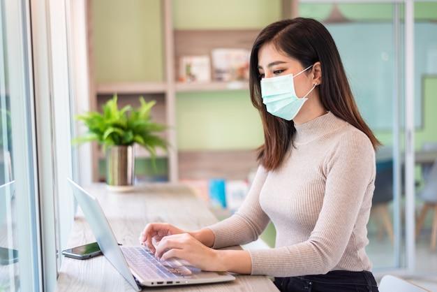 Donna che lavora al computer portatile mentre indossa maschera medica Foto Premium