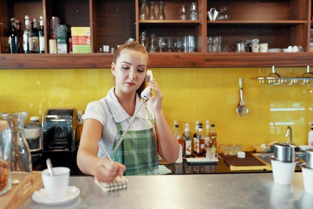 Donna che lavora come barista prendendo l'ordine del telefono Foto Gratuite