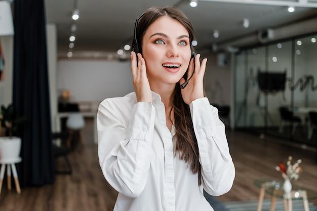 Donna che lavora in call center come operatore di assistenza clienti rispondendo alle chiamate Foto Premium