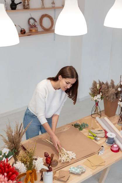 Donna che lavora nel suo negozio di fiori Foto Gratuite
