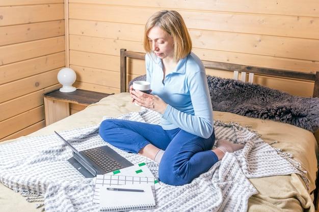 Donna che lavora per il computer portatile da casa sul letto. ragazza che per mezzo del computer portatile per la scrittura sulla tastiera nel suo ufficio con la tazza di caffè Foto Premium