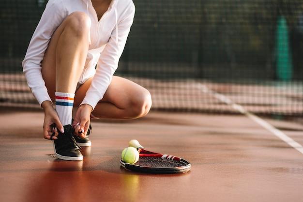 Donna che lega i lacci delle scarpe prima dell'allenamento Foto Gratuite